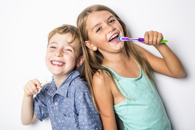 sister and brother brushing teeth