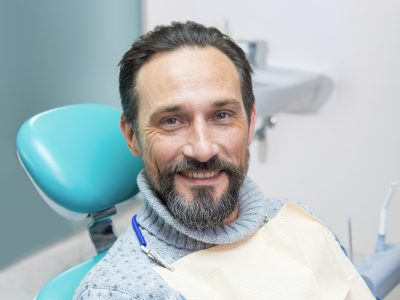 man in turtleneck in dental chair